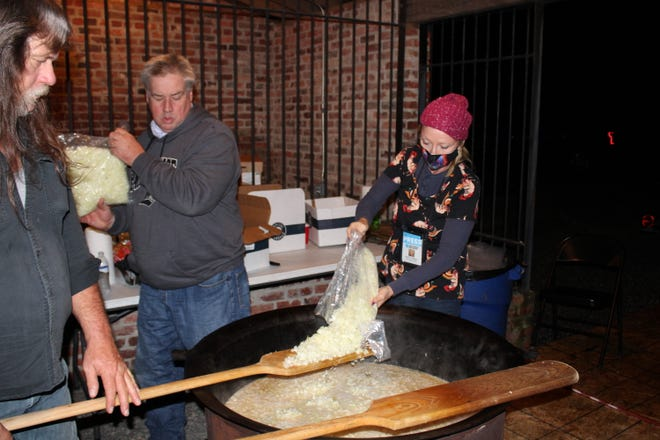 From left to right, stew master Ray Easter holds the paddle while Bill Jordan and the Social Butterfly Kristi K. Higgins add chopped onions to the Brunswick stew being made at the historic Peter Jones Trading Station in Old Towne Petersburg on Oct. 17, 2020.