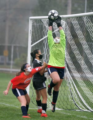 Toll Gate goalie Kylie Whitney goes airborne for the ball as teammate Victoria Halstead and Pilgrim's Katie Ignagni move in during Tuesday's game. Pigrim won, 5-1. [The Providence Journal / Kris Craig]
