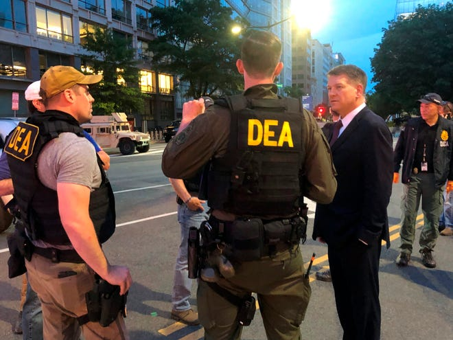In this Wednesday, June 3, 2020, photo Acting Drug Enforcement Administrator Timothy Shea, right, visits with DEA agents at a checkpoint in Washington. More than 1,500 people have been arrested in the last three months as part of a Drug Enforcement Administration project focusing on violent crime.  (AP Photo/Mike Balsamo)