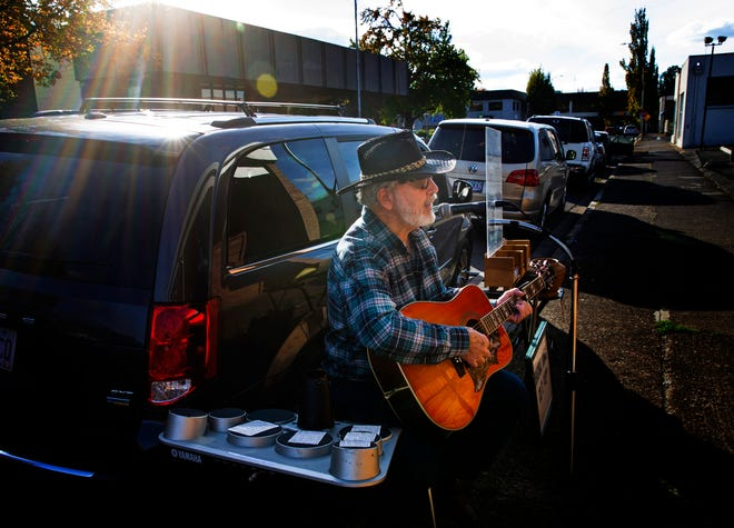 Paul Hash plays music on the sidewalk in front of the U.S. Post Office in Springfield.