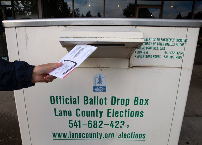 A voter drops her ballot off at an official drop box on Tuesday in Eugene.