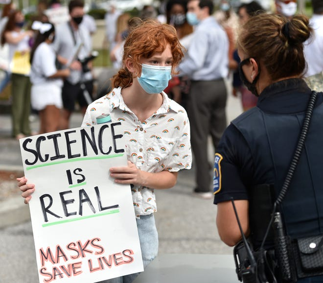 Mackenzie Valenza, 12, who is in seventh grade at Pine View, demonstrated outside the Sarasota County School Board building on Tuesday. She said she believes masks should be mandatory until there are almost no cases in America.