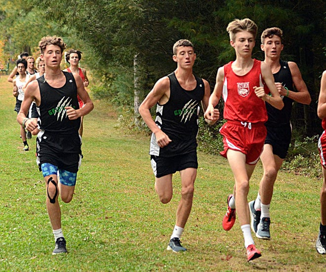 NFA's Peyton Ramsey runs with Griswold triplets Jacob Strain, left, Lucas Strain, and Michael Strain during a cross country meet last season in Norwich. [John Shishmanian/ NorwichBulletin.com]