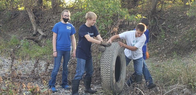 Collins-Maxwell FFA members removed several tires from Indian Creek as they helped with Nathan Smith's Eagle Scout project.