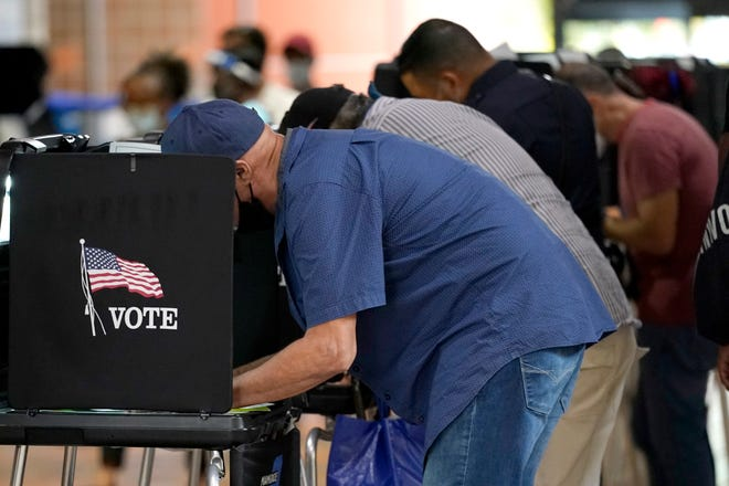 People vote at an early voting site Monday in Miami.