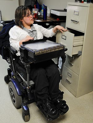 A woman with cerebral palsy works in an office.