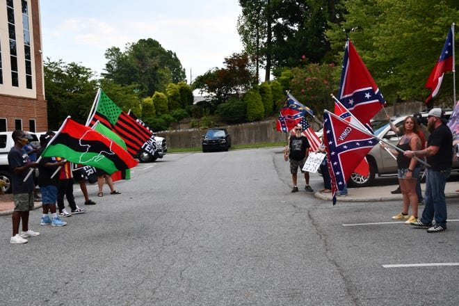 Monument protestors and counter-protestors gather outside a Davidson County meeting early in the summer. Both sides spent the summer clashing over the Confederate monument in Lexington. Elon University poll shows a growing divide between those who want to keep Confederate monuments and those who want them taken down.