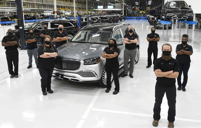 Mercedes-Benz U.S. International team members stand with the Mercedes-Maybach automobile. The luxury SUV is produced at the MBUSI plant in Tuscaloosa County. [Handout Photo]