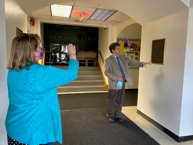 Judy Hengstebeck, Gahanna-Jefferson Public Schools communications coordinator, takes a photo of Superintendent Steve Barrett as he looks at a plaque that notes a portion of Lincoln High School being built in 1927. Across from the 1927 plaque is another marker, noting the building was renovated in 1987.