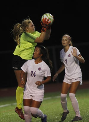 Olentangy Orange's Amanda Poorbaugh makes a save between teammates Elizabeth Woo, left, and Kaitlyn Colvert on Sept. 3 at Thomas Worthington. Poorbaugh, a Penn State recruit, has allowed eight goals and posted 10 shutouts in 17 games this season.