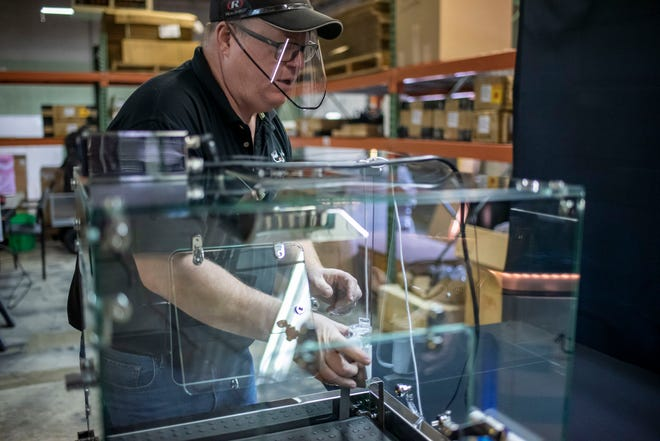 Ken Sunden, inventor of Puppywarmer, adjusts the nebulizer inside a Pro Series Incubator on Tuesday, Oct. 20, 2020 in Battle Creek, Mich. The Puppywarmer company creates incubators that deliver warmth, oxygen and humidity to newborn puppies and other at-risk animals.
