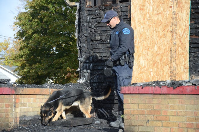 Trooper Mike Sinke and his dog, Cap, search the fire damaged home on Post Avenue on Tuesday morning.