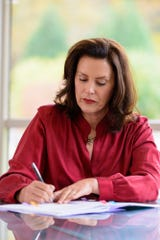 Gov. Gretchen Whitmer signs into law a six-week extension for unemployment benefits at her Lansing home on Tuesday, Oct. 20, 2020.