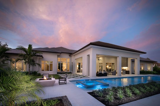 Streamsong Pool Dusk:  The great room in Seagate Development Group's recently sold Streamsong grand estate model at Quail West opens to a covered lanai with a fireplace, an island kitchen, conversation and dining areas, and a custom pool and spa.
