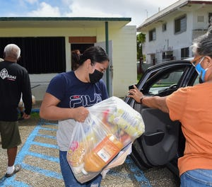 Office clerk Kimberly Salas helps load food orders into vehicles during a food distribution drive-thru at the Talofofo Mayor's Office on Oct. 20, 2020.