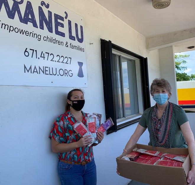 Samantha Taitano, executive director of Mañe'lu, accepts a donation of 100 GladRags reusable menstrual pads from Jayne Flores, Bureau of Women's Affairs director Oct. 20,