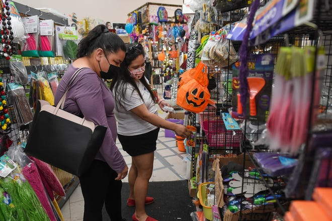 Lelani Taitague, left, and Andrea Quichocho shop the Underground Dungeon Halloween Store's selection of products in Harmon, Oct. 20, 2020.