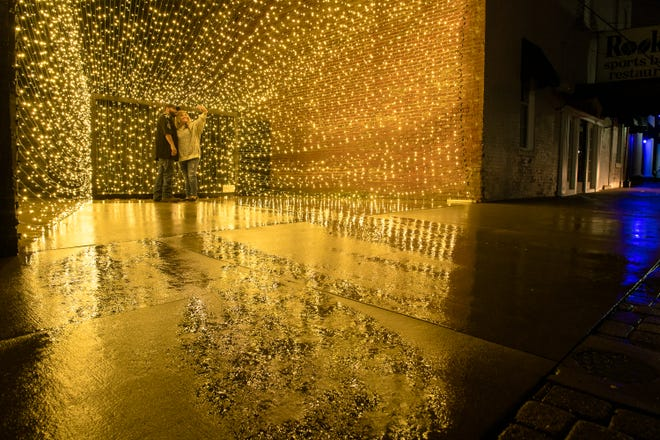 Gold color washes over the wet pavement as Lee and Kasey Biggs take a rainy night picture in the new 10,000 LED selfie spot next to Rookies on Second Street in Henderson Monday, October 19, 2020.