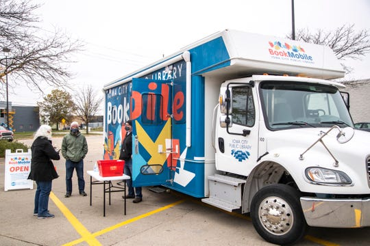 Heidi Lauritzen, left, picks up a reservation of books from librarians Tom Jordan and Paul Bethke, right, during an Iowa City Public Library Bookmobile stop, Tuesday, Oct. 20, 2020, at the Waterfront Hy-Vee parking lot in Iowa City, Iowa.