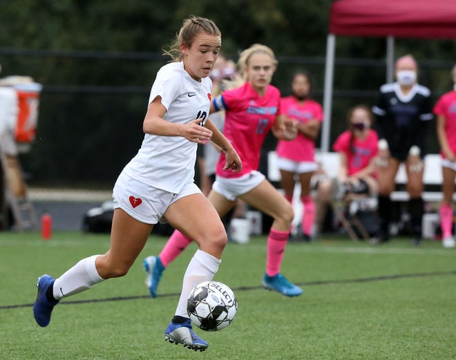 Sacred Heart's Mallory Glass (10) fights pressure from Assumption's Kate Widman (12) during the the Seventh Region girls soccer semifinals at Assumption Green Champions Trace in Louisville, Kentucky.     October 19,  2020.