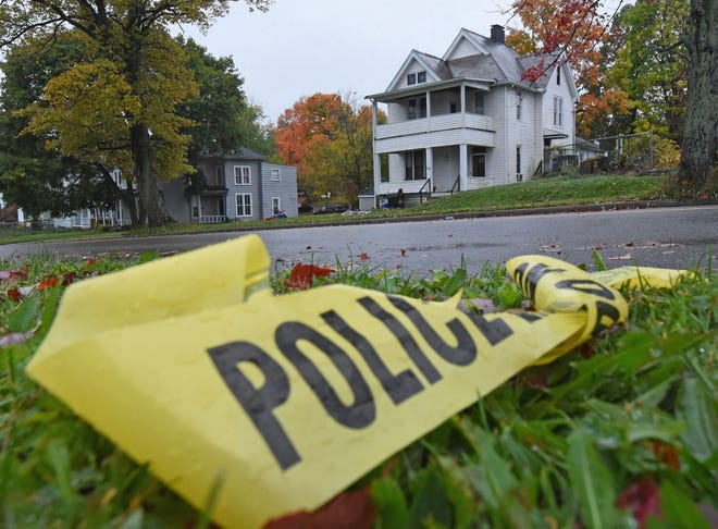 Police tape lies on the ground across the street from 136 Sturges Avenue where at least five people were injured by gunfire in a drive-by shooting Monday night.