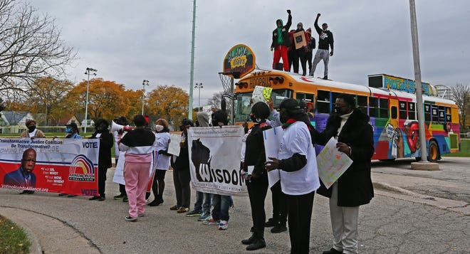Members from the Voter Awareness March and Caravan get voters excited from a distance at the Clinton Rose Senior Center at 3045 N. King Drive on Oct. 20, the first day of early voting in Milwaukee.