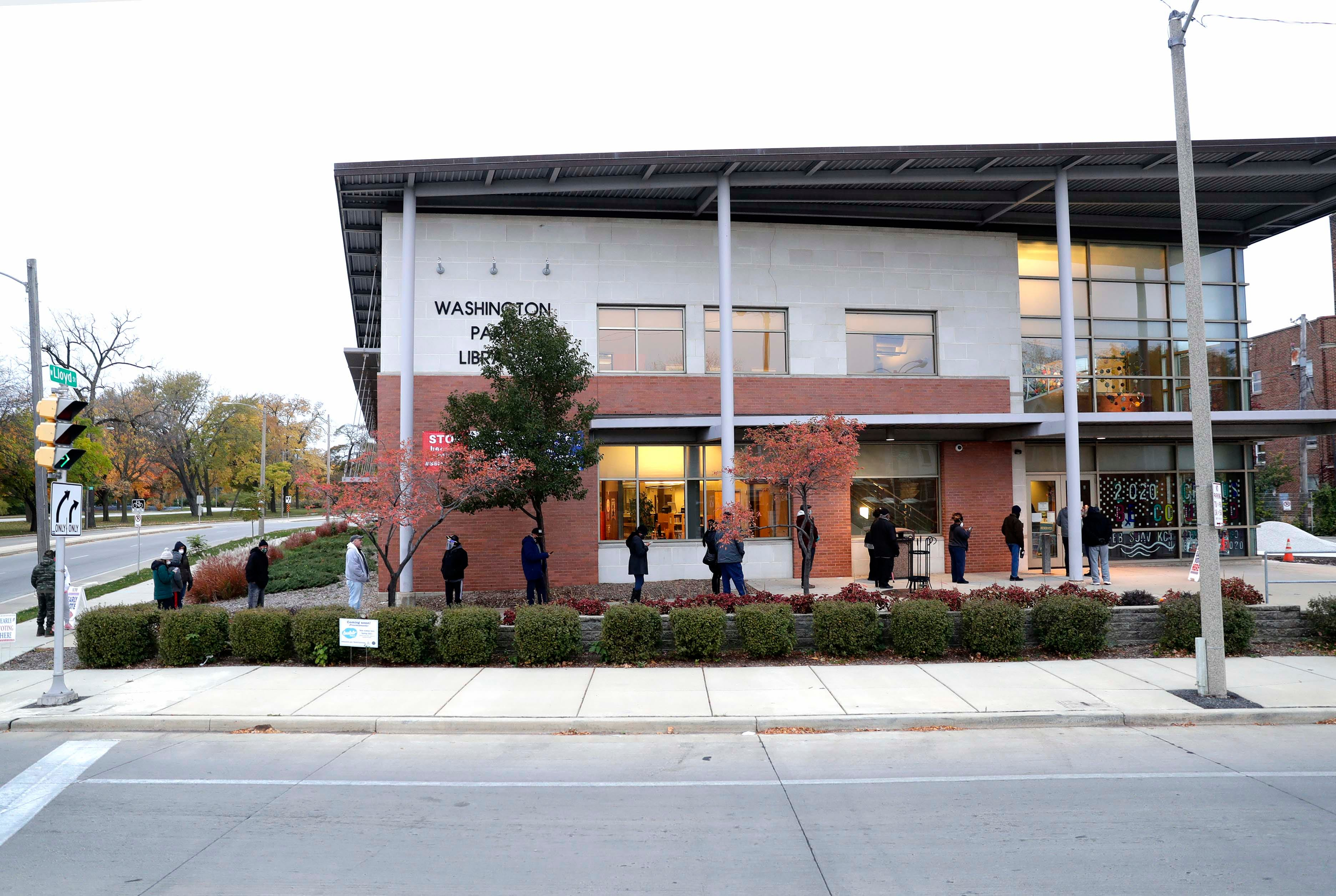 Milwaukee residents are lined up early outside the Washington Park Library to cast their ballots during early voting.