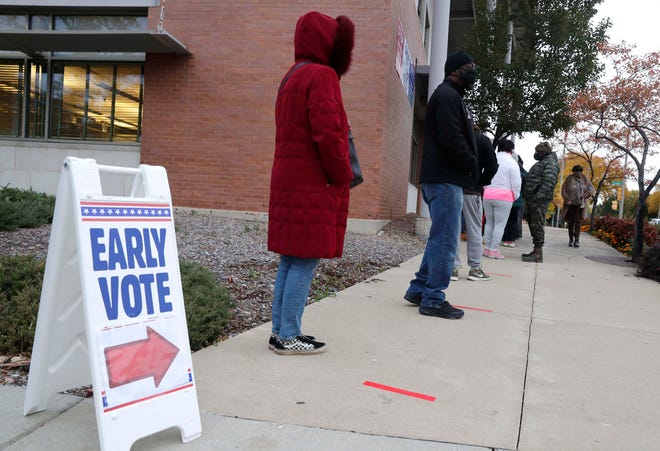 Milwaukee residents are lined up early outside the Washington Park Library to cast their ballots during early voting on Tuesday.