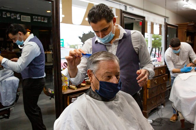 Luis Fuentes gives customer Jim Pacitti of Naples a haircut, Tuesday, Oct. 20, 2020, at ManGrove Mens Grooming Barbershop in East Naples.