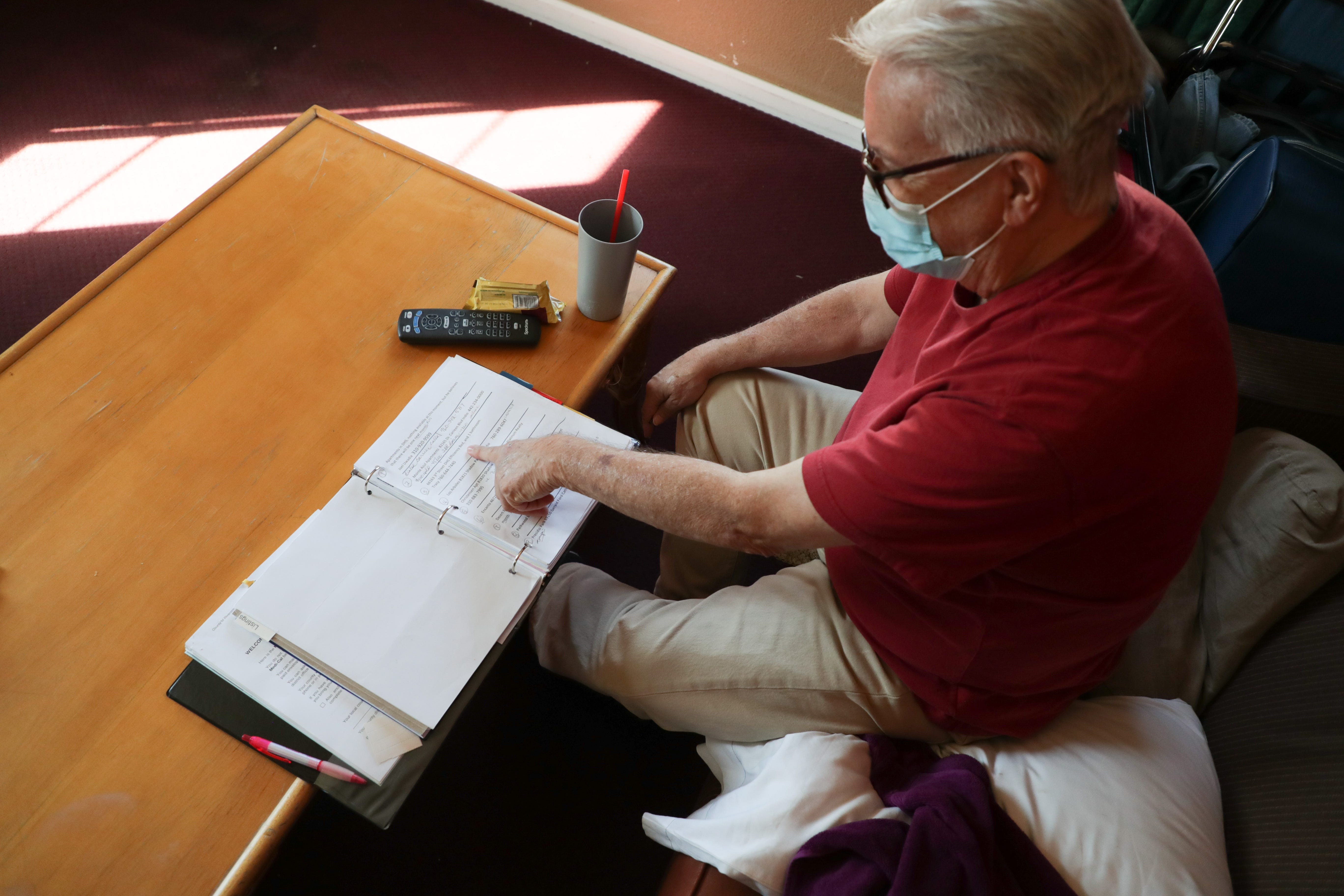 Lee Fournier sorts through a binder with potential housing options in his hotel room provided by Project Roomkey on Sunday, October 11, 2020, at Rodeway Inn & Suites in Indio, Calif. Project Roomkey is an effort by the state to house individuals experiencing homelessness during the COVID-19 pandemic.