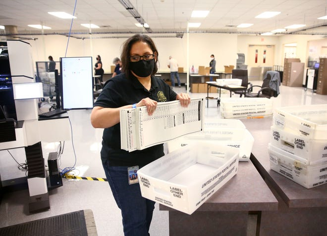 Mail-in ballots are tabulated at the Maricopa County Elections Headquarters in Phoenix on Oct. 20, 2020.