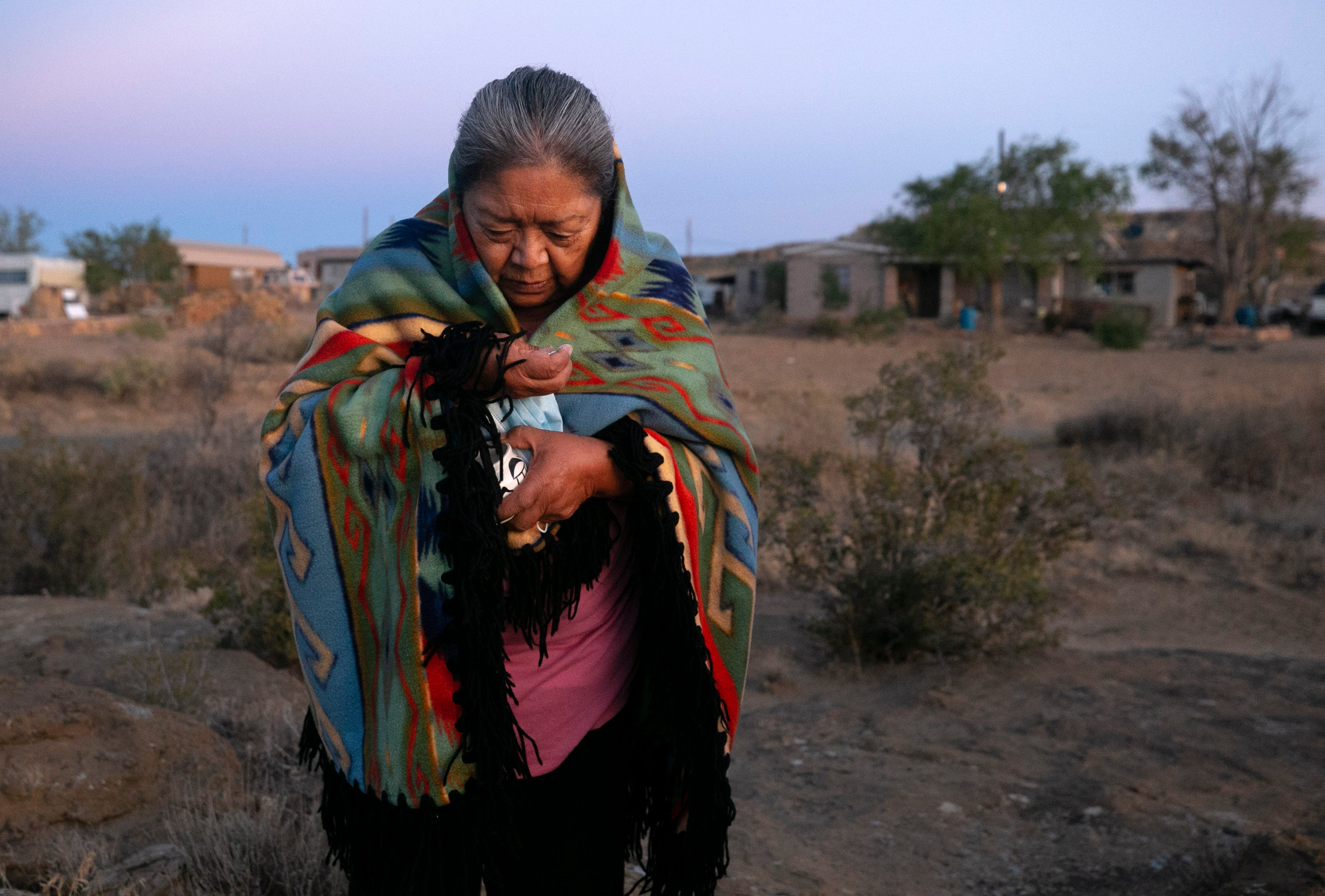 Beatrice Norton prays at sunrise while taking ground white corn in her hand in front of her home in Oraibi on the Hopi Reservation on Sept. 12, 2020.