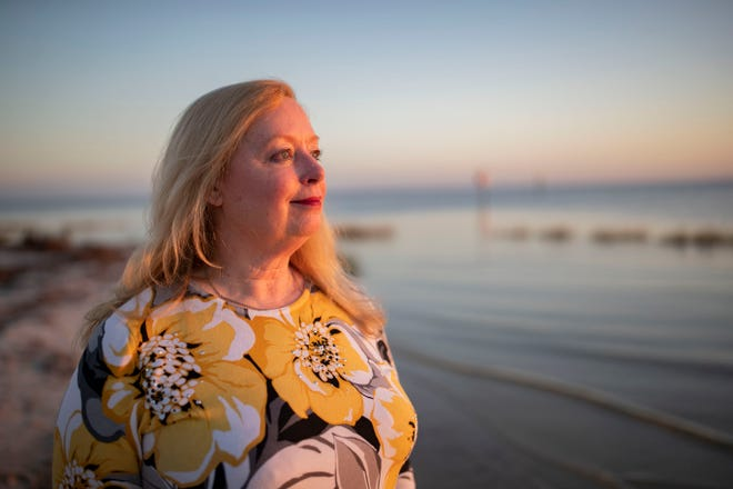 Jeanie Booth poses for a portrait on the shore of the beach in Shell Point, Florida.