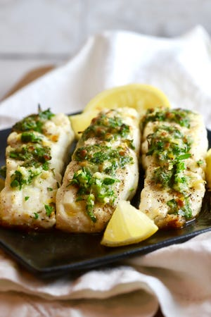 Gremolata, made with olive oil, garlic, lemon zest, parsley, and Parmesan cheese, tops this broiled halibut.
