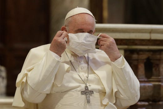 Pope Francis puts on his face mask as he attends an inter-religious ceremony for peace in the Basilica of Santa Maria in Aracoeli, in Rome Tuesday, Oct. 20, 2020.