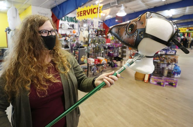 Meralie Pocock, who owns Mr. Fun's Costumes and Magic Emporium with her husband, Andy, puts a plague doctor mask on display at the store on Wednesday in Cuyahoga Falls.