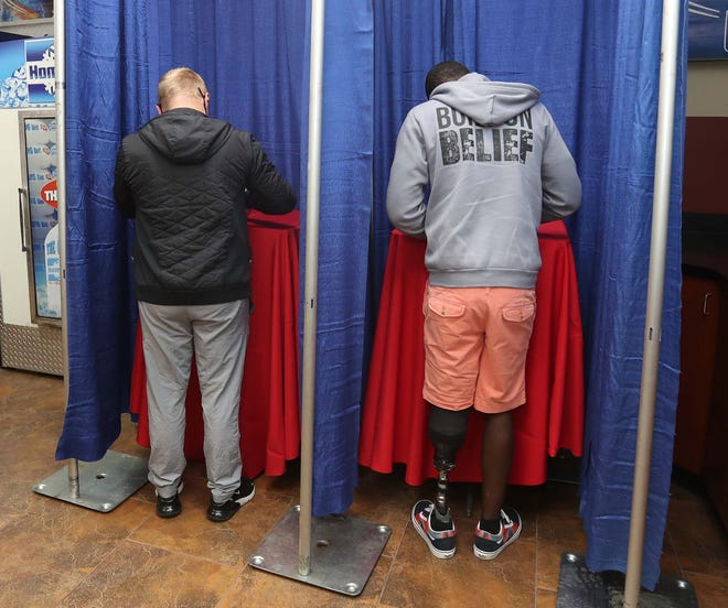 """Blake Gibbs, left, of Norton and Demetrius Palmer of Barberton participate in mock voting Wednesday at Rocky's Gas in Barberton. Store owner Shaun """"Rocky"""" Jaber says he wants to educate people about voting."""