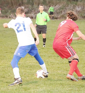 Northwestern's John Widdows (21) tries to maneuver the ball past Loudonville's Trevor Portz (9) during a Division III sectional semifinal game Tuesday night at Redbird Soccer Stadium. The visiting Huskies won, 3-0.