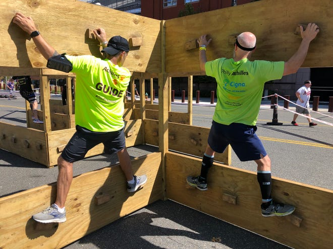 Achilles athlete Matt McAvoy (right) competes on the Z-wall in the Spartan Stadion obstacle race in Philadelphia along with guide Anthony Rewinski at Citizens Bank Park on Sept. 21, 2019.