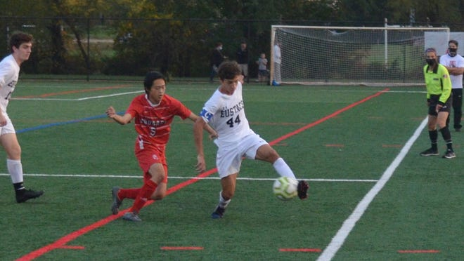Bishop Eustace captain Johnny Verecchia (44) tries to turn the corner at midfield with Alan Zheng of Cherry Hill East in pursuit during Tuesday's Olympic Conference game.