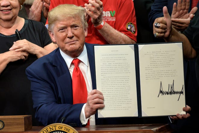 President Donald Trump signs an executive order on Medicare at the Sharon L. Morse Performing Arts Center in The Villages in October 2019.
