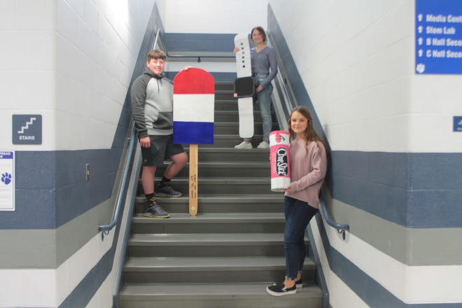 Cambridge High School students display the pieces of pop art they created from recycled materials. The students were tasked to come up with their own ideas for the art assignment. Lainey Carpenter created an Apple watch, Caiden Dillon, a popsicle, and Kendal Kenworthy, a tube of Chapstick.