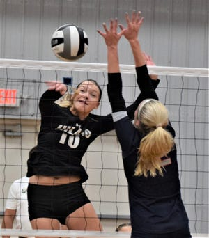 Sara Schlabach drives a spike past the block attempt by Morgan's Ella Morrow.