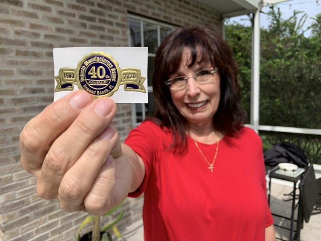 Jayne Fifer, president and CEO of the Volusia Manufacturers Association, holds a sticker made for the group's 40th anniversary this year at her Ormond Beach home on Tuesday, Oct. 20, 2020. The coronavirus pandemic forced the VMA's planned 40th anniversary celebrations to be postponed until 2021 but the group still plans to hold its annual golf tournament in November and its annual awards event will be held virtually via video in December.