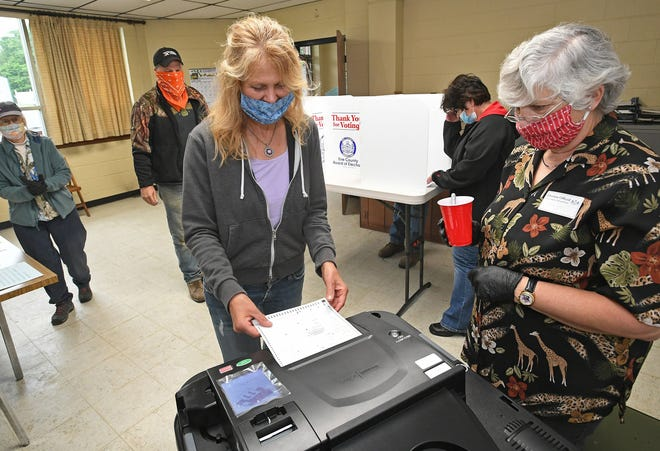 Sherri Porter feeds her ballot into a scanner after voting in the primary election at the LeBoeuf Township polling place at the LeBoeuf Township Municipal Building in June. Erie County officials hope voters will contact them with questions about the Nov. 3 election.