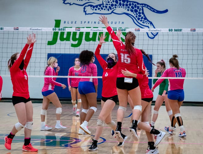 Blue Springs' Lily Letchworth (15) leaps into the arms of teammates to celebrate the final point in a 3-0 win over rival Blue Springs South in the annual Dig Pink match.