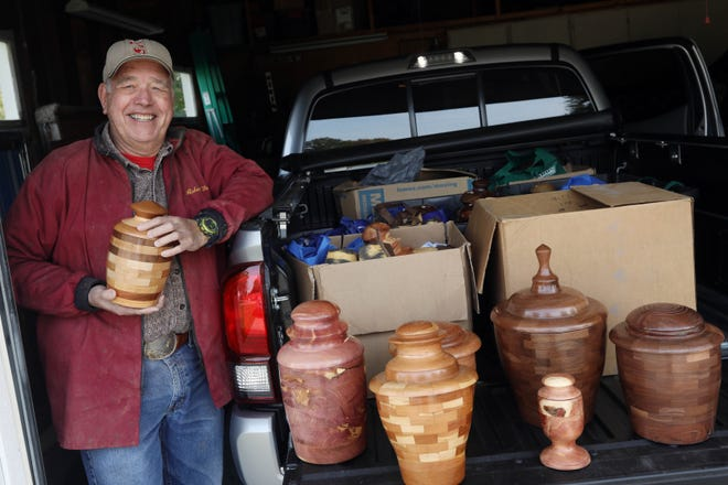 John Hunerdosse is shown Wednesday, Oct. 21, with some of the 30 handmade burial urns he plans to take to funeral homes at his West Burlington home. Hunerdosse spends four to five hours a day in his workshop making urns from walnut, cherry, oak, ash and maple.