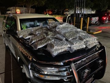 Plastic bags of marijuana weighing 150 pounds sit on a Florida Highway Patrol cruiser's hood after a traffic stop and arrest Tuesday night on I-95.