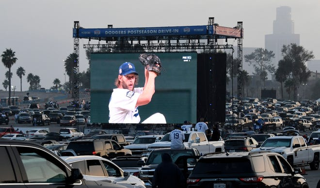 Clayton Kershaw of the Los Angeles Dodgers pitches as fans look on a giant screen during Game 1 of the World Series between the Tampa Bay Rays and the Los Angeles Dodgers in the parking lot of Dodger Stadium in Los Angeles on Tuesday.