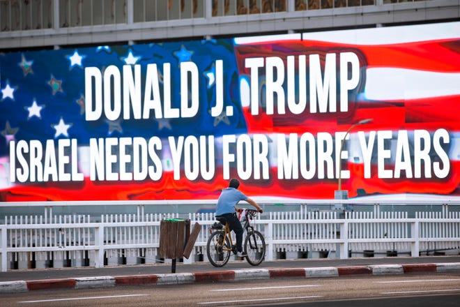 A cyclist rides next to a billboard supporting President Donald Trump, ahead of the U.S presidential election, in Tel Aviv, Israel, on Wednesday.